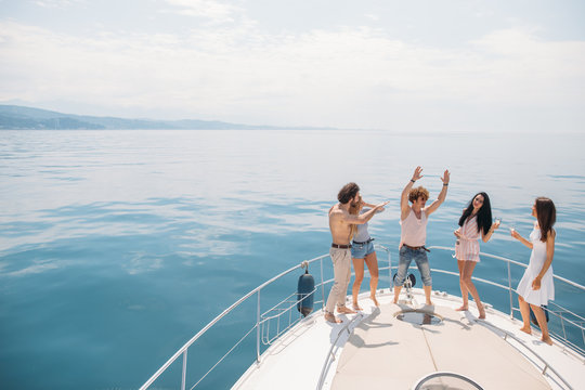 Luxury vacation. Joyful young male and female friends dancing and having fun on a bow of sailing boat deck, smiling, hugging over amazing blue marine background with copyspace. Banner.
