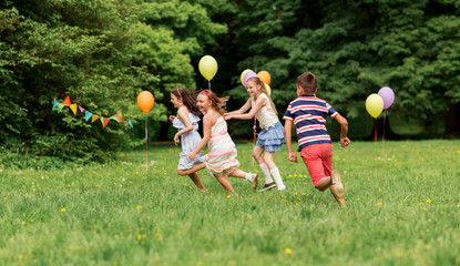 friendship, childhood, leisure and people concept - group of happy kids or friends playing tag game at birthday party in summer park