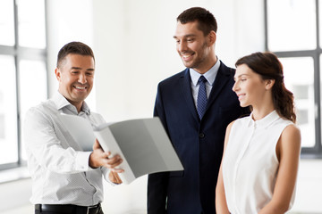 real estate business, sale and people concept - happy smiling realtor with folder showing documents to customers at new office room