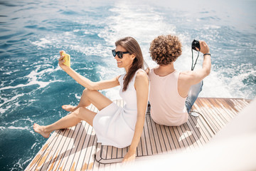 Vacation, sailing, tourism, travel and people concept - happy young couple with smartphone taking selfie on sail boat or yacht deck floating in seavover amazing sea background