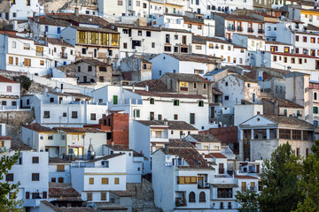 Houses and roofs next to mountain limestone, view to the mountains of the river Jucar, take in Alcala del Jucar, Albacete province, Spain