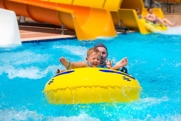 Dad and little son having fun on waterslide during sun holidays