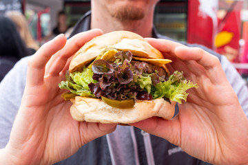 Man is holding an organic vegan burger with seitan patty in his hands during a street food festival