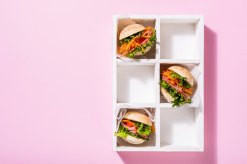 Homemade mini burgers with ham, tomato, carrot, fresh salad served in old white wooben box on pink background. Healthy junk food concept with copy space.