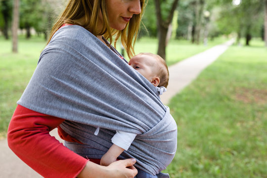 Mother holding baby in scarf baby carries outdoor