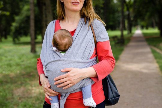 Mother holding baby in baby scarf carrier and walking outdoor in park