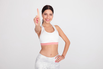 sexy fit woman in white gym outfit pointing finger up