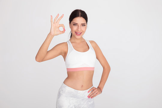 happy fit woman makes perfect fingers sign while standing