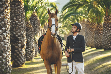 Portrait of young handsome horserider close to his brown horse in a palm trees avenue on summer day at sunset