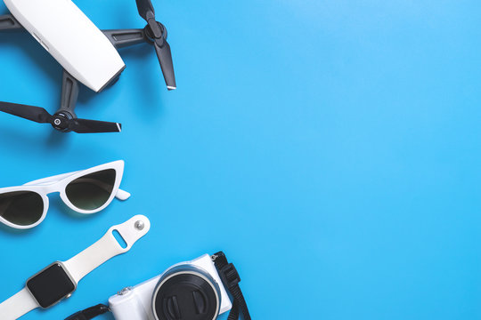 Hi tech travel gadget and accessories on blue copy space