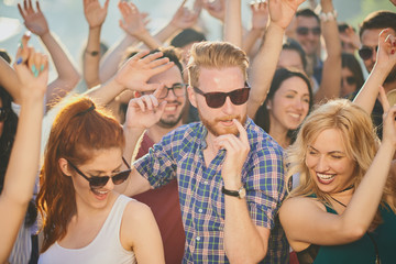 Group of people dancing and having a good time at the outdoor party/music festival