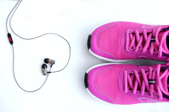 Pink running shoes for women and headphones on a white background
