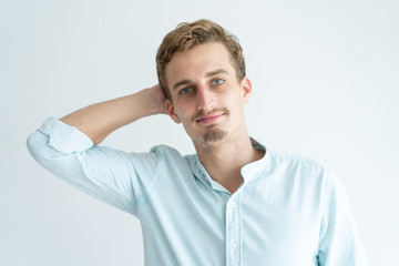Relaxed young man holding hand behind head and looking at camera. Handsome guy having break. Relaxed man concept. Isolated front view on white background.