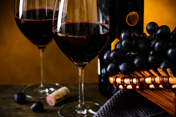 Still life with bottle of red wine, two wineglasses and grape in