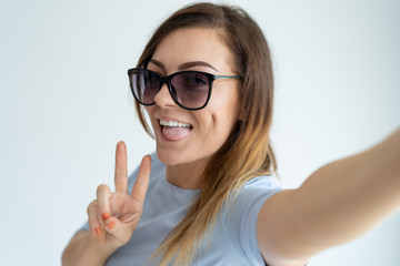 Smiling beautiful woman taking selfie photo, showing victory sign and looking at camera. Playful lady putting out tongue. Selfie photo concept. Isolated view on white background.