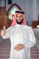 Arab man showing thumbs up at mosque