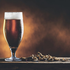 Beer glass with dark cold beer with drops of water and peanuts o