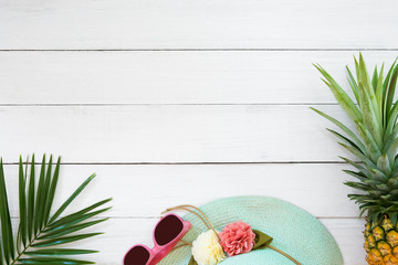 Concept of tropical fruit. Pineapple, straw hat, sunglasses and palm branch on wood plank white color. Summer vacation background and top view design