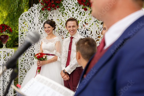 Hy Handsome Groom And Lovely Bride Smiling During Preacher Sch Outdoor Wedding Ceremony