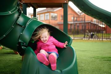 Cute little girl having fun on outdoor playground