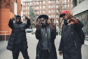 three young men posing outdoor looking camera serious - rap crew, gang, swag concept