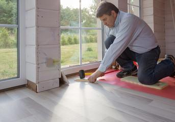 Man installing new laminated wooden floor on wooden house, scandinavian style.
