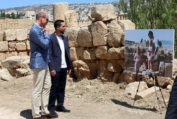 Britain's Prince William and Jordan's Crown Prince Hussein look at a photograph showing William's wife, Catherine, the Duchess of Cambridge, the former Kate Middleton, her father Michael and younger sister Pippa in the ruins of the Roman city of Jerash