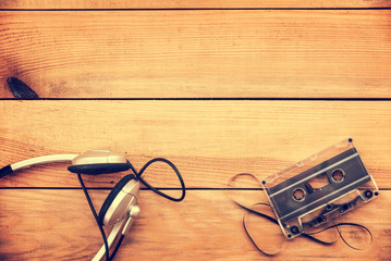 Headphones and translucent audio cassette tape on vintage wood planks  background white copy space