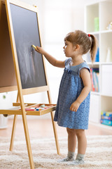 Little child girl draws with chalk on the blackboard