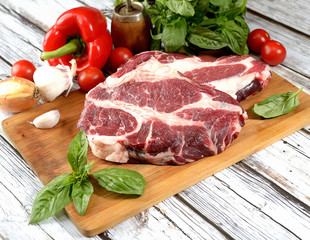 fresh raw meat, herbs and spices on a cutting board on a wooden background