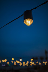Warm light bulb and dark blue sky