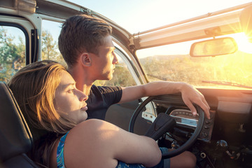 Couple looking at sunset in a car