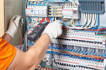Engineer tests power high voltage three phase circuit box with multimeter.