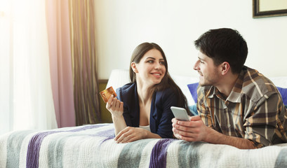 Happy couple shopping online with credit card and smartphone