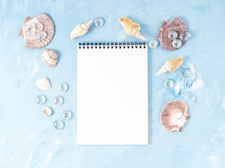Mock up with frame of seashell, notepad on blue stone backdrop, copy space. Summer concept of holiday by sea