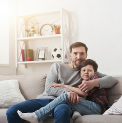 Dad and his son hugging on sofa at home