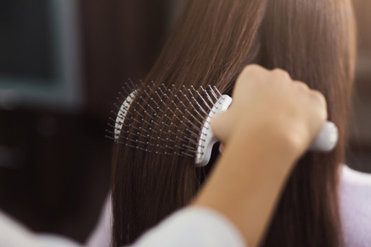 Hairdresser combing hair with brush