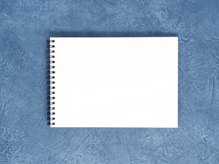 The open notepad with clean white page on aged dark blue stone table, top view