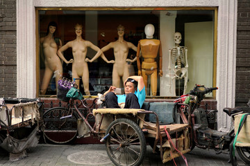 A man looks at his mobile phone on a tricycle outside a mannequin shop in Shanghai