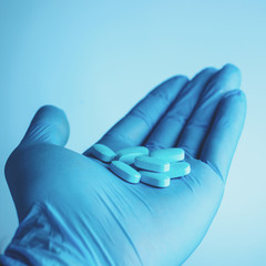 Blue pills in doctors hand on blue background. Life save service