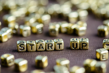 Motivation word START UP made from small golden letters on the b