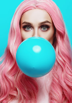 Beautiful young woman face close up, blowing a balloon
