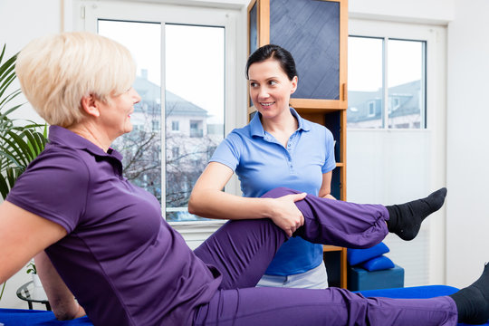 Therapist checking knee joint of senior woman