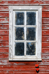 Barn window with rustic antique red hearts hanging from rope