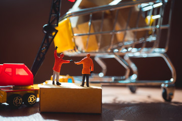 Miniature people, engineer working at construction site with mini shopping cart using as business, industrial and logistics concept