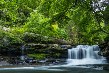 A forest waterfall with motion and large stones deep in a forest.