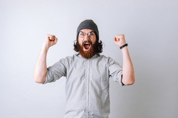 Young strong curly haired bearded man screaming, yelling winner wearing glasses and white shirt.