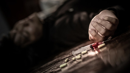 Junkie man lying on the floor near drug injection syringe and pills. Death from drug overdose and addiction concept
