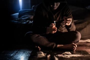 Junkie man preparing heroin dose by using spoon and cigarette lighter for melting, Syringe for injection. Hard drug overdose and addiction concept