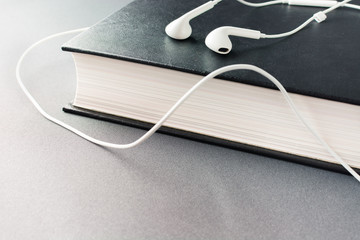 White headphones lie on a thick black book